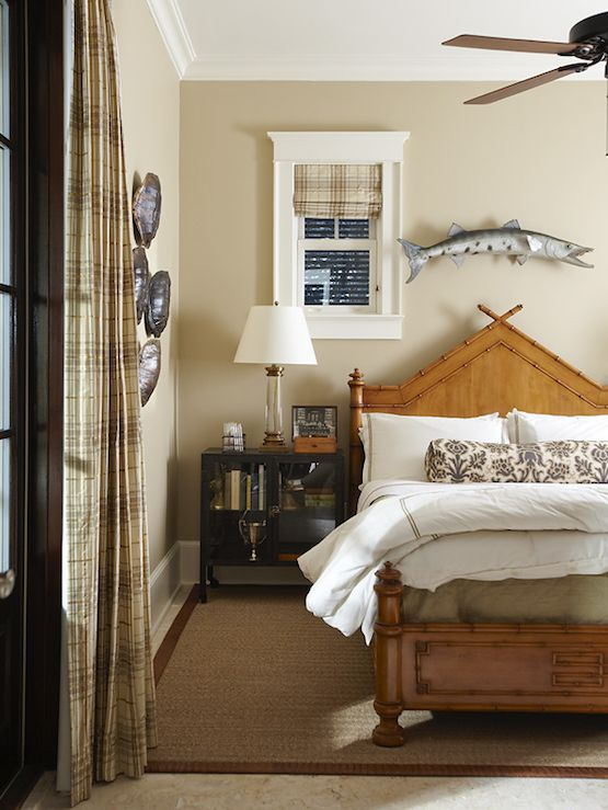 Urban Grace Interiors  Chic boy's room design with tan walls paint color, faux bamboo bed, sisal rug, blue & brown floral lumbar pillow, plaid window panels, plaid fabric roman shade, fish art and glass column lamp.