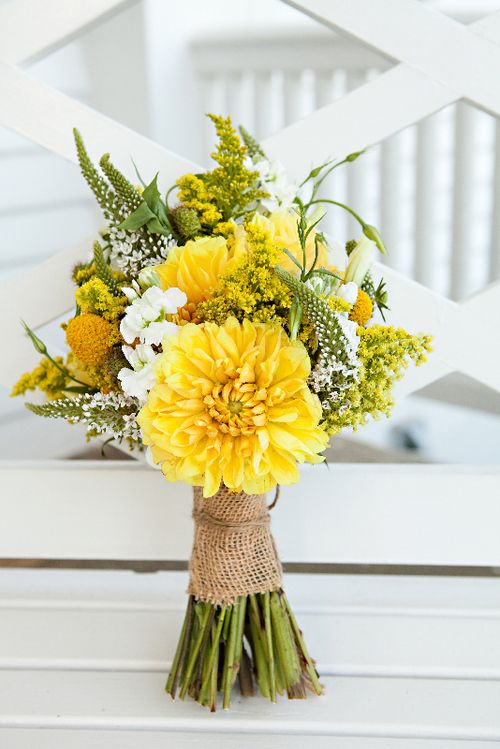 Yellow flowers wrapped in burlap is perfect for a rustic wedding
