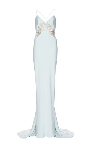 This **Elizabeth Fillmore** gown is rendered in silk crepe and features a v-neck with metallic lace applique at the bodice, a backless design with crossed camisole-style straps, and a slip dress silhouette with a small train.