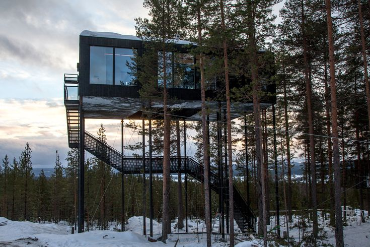 Guests ascend a staircase into the cabin, while a small lift carries up their luggage.