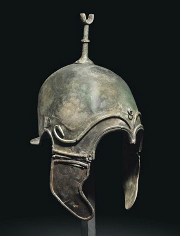 A GREEK BRONZE HELMET OF CHALCIDIAN TYPE   LATE CLASSICAL PERIOD, CIRCA LATE 4TH CENTURY B.C.   Formed of a single heavy sheet, the domed crown with tall crest-holder, short flaring neck-guard, helmet and cheekpieces edged with a separately-applied moulded band, similar separately-applied brows with bud-like terminals, rivet with attachment ring at front, two attachment sockets either side, back of helmet and cheekpieces pierced once  13½ in. (34.3 cm.) high incl. cheekpieces