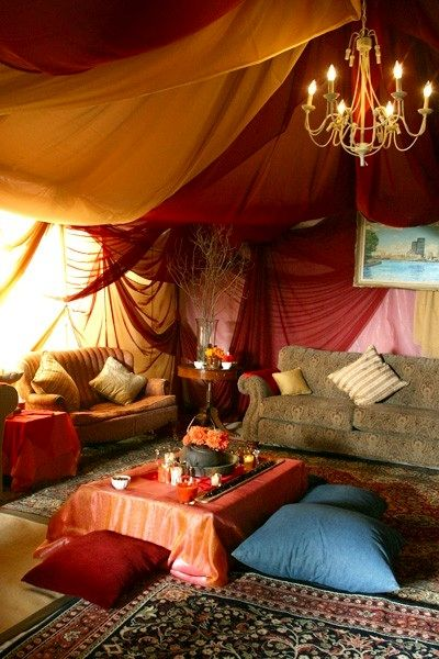 Bohemian chic living space - draped fabric, layered rugs, floor pillows, comfy vintage sofas, stunning chandelier and warm boho tones.