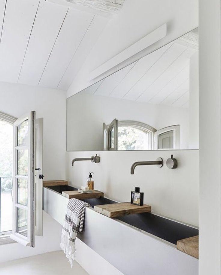 White modern bath with an elongated trough sink, high faucets.