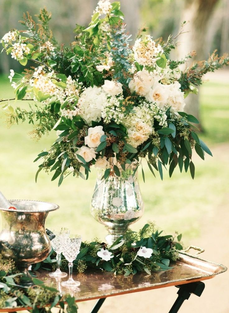 garden style design with darker foliage makes the blush/peach/pale pink flowers really pop. in silver vase
