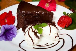 Homemade Warm Chocolate Cake with rich fudge sauce, served with cream or ice cream — at Stefanos Italian Pizza And Pasta.