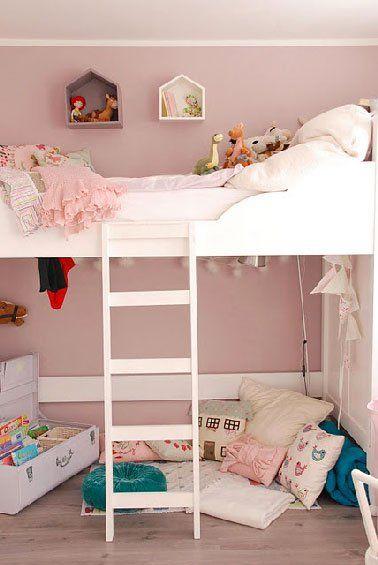 Une ambiance couleur tout en douceur pour une chambre de fille avec une peinture rose poudré autour du lit superposé blanc et des nuances de rose pour ses coussins et bibelots.