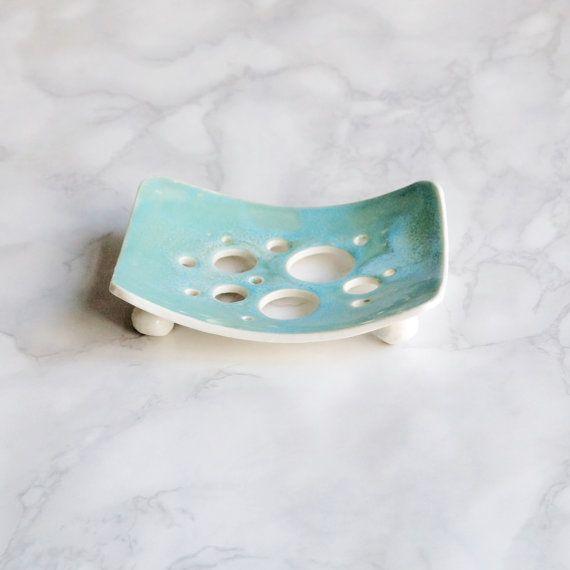 Handgemachte Keramik-Porzellan-Seifenschale mit einem Aqua Glasur und Blase Löchern. Gebogene Form, die meisten Seifen zu halten. Türkis / Aqua glänzende Glasur. Löcher um die Seife abfließen zu lassen. Porzellan-Kugelfüßen. Seife Teller ca. 80 mm x 104 mm Bitte leichte Unterschiede in der Glasur durch die handgemachte Prozesse ermöglichen. Ihnen wird genau so schön wie den hier gezeigten sein. Als Grafik-Designer bin ich zu entwerfen Logos mit minimalen Details und maximale Wirkung v…