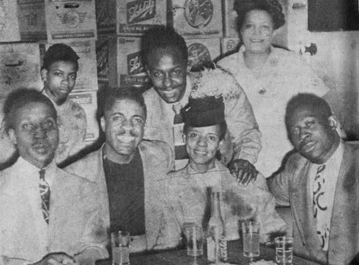 "John Lee ""Sonny Boy"" & Lacey Belle Williamson, Muddy Waters (left) and Eddie Boyd (standing), mid 1940s at the Club Georgia on Chicago's south side; others are Andrew 'Bo' Bolton (Muddy's long time chauffeur, right), the woman standing is Mrs. White, wife of the club owner, the boy on the left is Mrs. White's son, who helped out at the club; source: Mike Rowe: Chicago Blues - The City and the Music.- NY (Da Capo Paperback) 1975, p. 42 (credited to ""Chess Records""); photoshopped by Stefan…"
