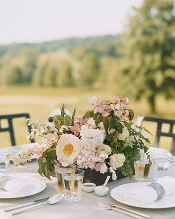 Centerpieces set in low wooden trays with peonies, viburnum, dogwood, green parrot tulips, spirea, sweetpeas, double lilacs, maidenhair fern, and fiddleheads are great for outdoor weddings