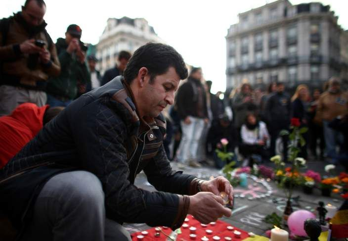 People leave tributes at Brussel's Place de la Bourse following the attacks on the city