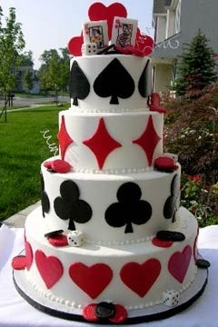 A very unique four tier red and white wedding cake decorated with black and red suits from the deck of playing cards.