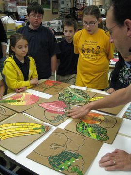 The kids use cut-up paint chips to create their mosaic masterpieces.