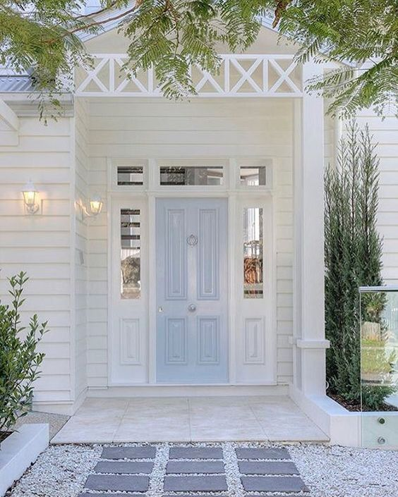 Charming light blue door on white house with amazing curb appeal.