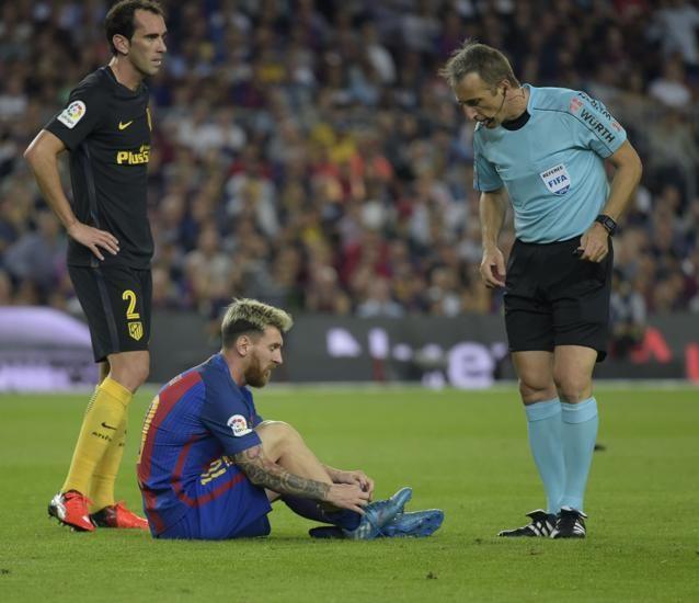 Messi lesionado es atendido por el árbitro.