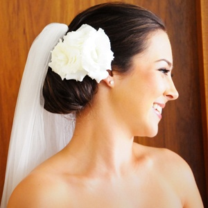 Alexandra wore her hair in an elegant updo with large flower to the side of cathedral length veil.    Photographer: The Hayman Gallery