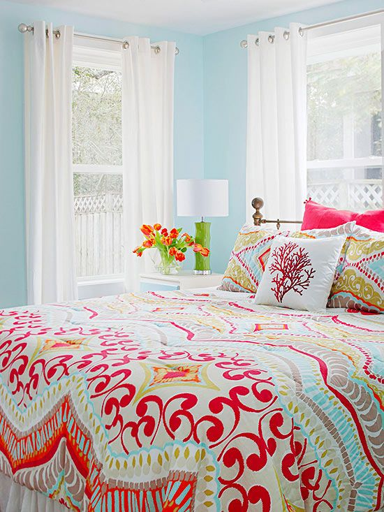 One of the easiest ways to get a colorful bedroom is to start with colorful bedding and build your color scheme from there. Pull out one color for the walls and other colors for accessories, but don't feel like you need to color everything. Here, billowy, white curtains ensure the bright bedroom is still livable./