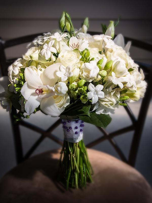 Bridal bouquet of roses, Cymbidium orchids, stephanotis, freesia, lisianthus and alstroemeria