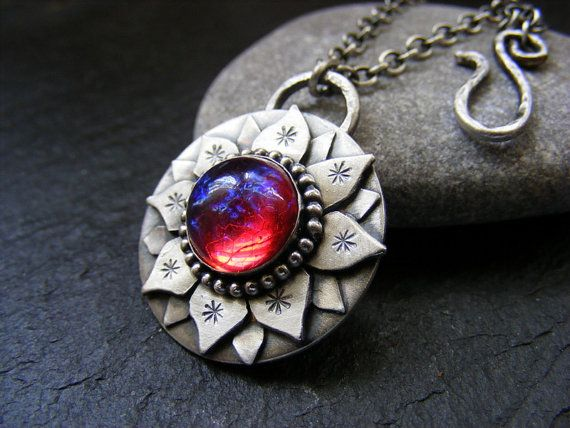 This is a silver lotus flower hand sawn pendant with a stunning dragons breath cabochon for  decoration , This is a real eye catching piece  In the