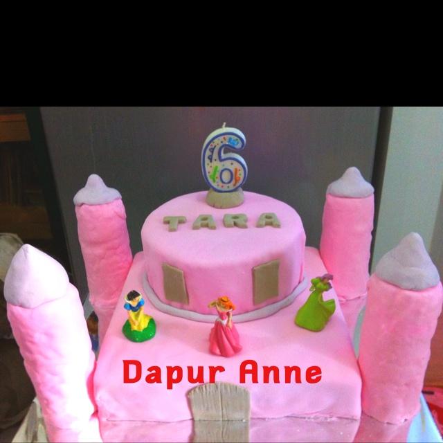 Castle birthday cake with princess figurines..