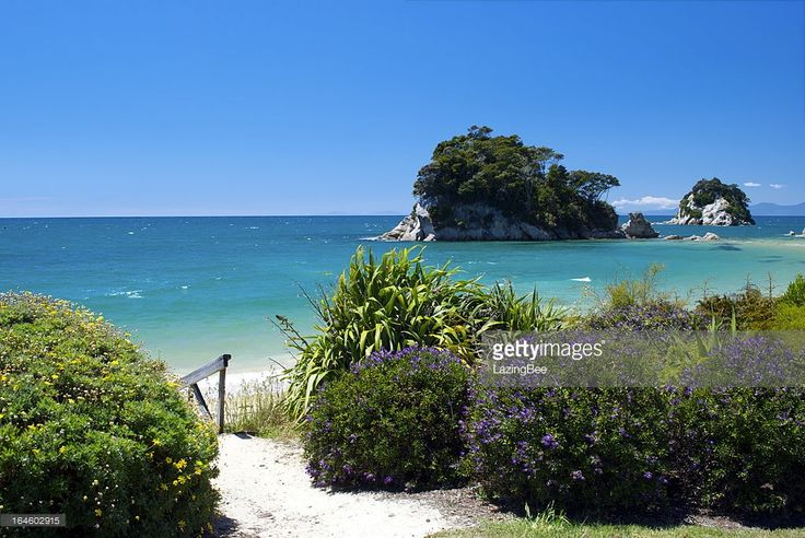 Looking across Little Kaiteriteri Beach's still waters to Torlesse Rock, Kaiteriteri, Tasman Region, New Zealand in summer.