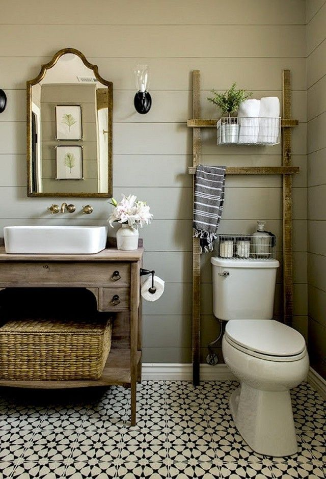 Rustic bathroom with paneling, a vintage mirror, and printed tile floors