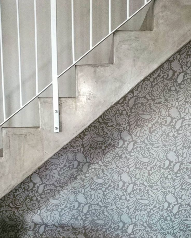 A gray and white stenciled accent wall under the stairs using the Paisley Allover Stencil from Cutting Edge Stencils. http://www.cuttingedgestencils.com/paisley-allover-stencil.html