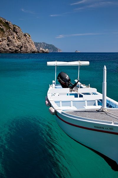 Boat moored on clear water of Paleokastritsa, Corfu Greece