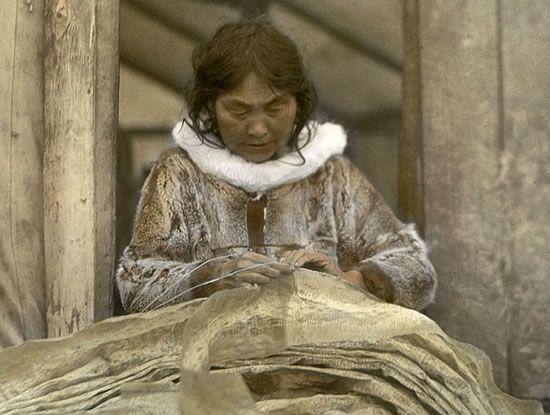 Yupik woman sewing.  Wearing sealskin parky w/sunshine ruff
