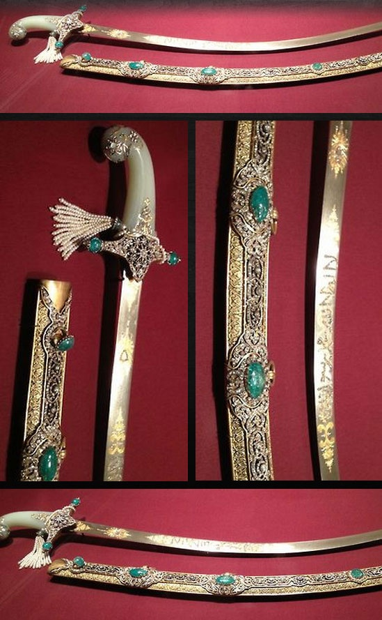 """The sword was probably assembled by a court jeweler, using a 17th century Iranian blade, an 18th century Indian jade grip and a gem-studded gold and gilt-brass mounts of contemporary workmanship. The emerald near the top of the scabbard opens to reveal a secret compartment containing a gold coin marked with the name Süleyman the Magnificent (1494-1566), the most powerful Ottoman ruler of the 16th century. The underside of the emerald is inscribed with the phrase """"According to God's will."""""""