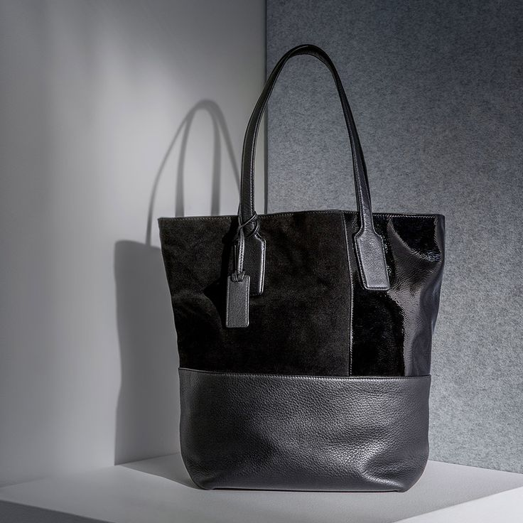 The classic leather tote reimagined with patent leather panels and black hardware.