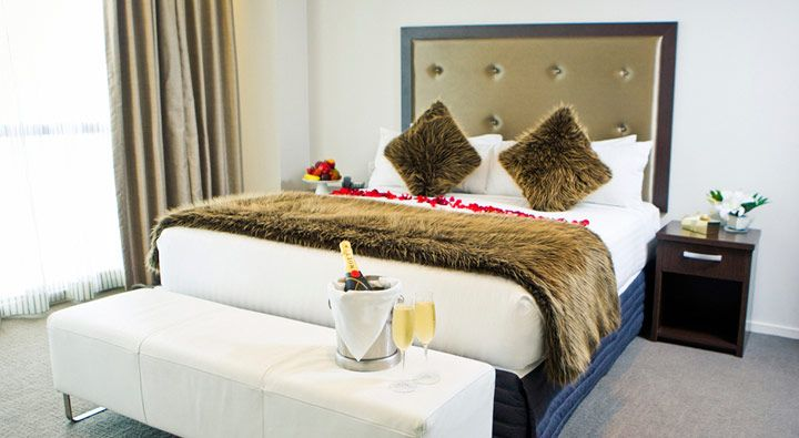 A Luxury Executive King Suite bedroom at Rydges Auckland.