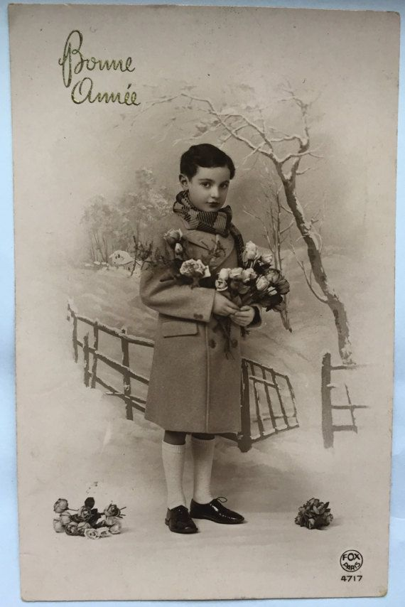 French little boy in warm winter holding flowers * Happy New Year greeting card * Sepia photograph early 1910s