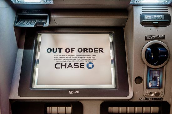 Indigenous Advocates launched an art intervention, by placing Out of Order signs on ATMs at various locations of JP Morgan Chase in Manhattan, calling on New York City Mayor Bill de Blasio and Comptroller Scott Stringer to use their positions on the NYC Banking Commission to to end the city's relationship with JPMorgan Chase and other banks funding pipelines like the Dakota Access Pipeline (DAPL).