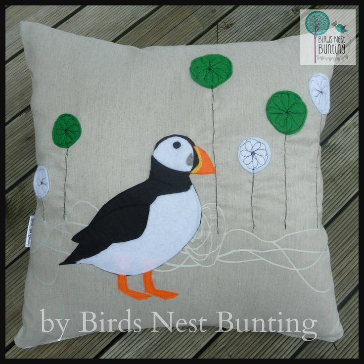 Puffin Cushion by Birds Nest Bunting. A felt puffin appliqued to sandy coloured fabric, the flowers are free motion embroidered- a tricky new skill!