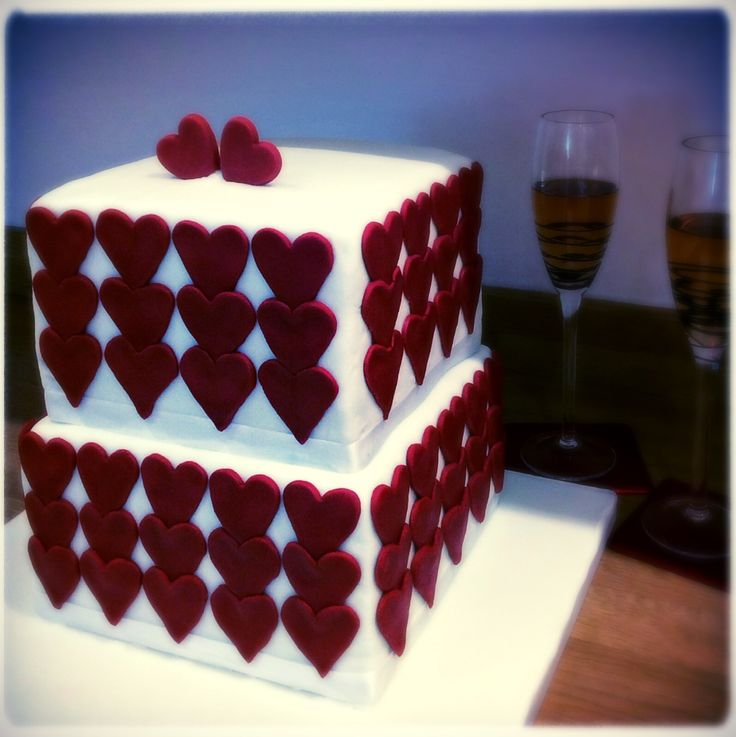 2 tier square and hearts ruby wedding anniversary cake with heart topper. Could make for a stunning contemporary wedding cake too. Made by the White Rose Bakery in Tavistock, Devon @wrbakery Facebook /whiterosebakeryuk