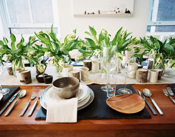 A fun dining idea courtesy o Brad Ford: replace your placemats with slate platters!  Ford mixed aged silver cutlery with wood chargers, a hemp-like table runner, and birch-wrapped votives to create a textural, earthy tablescape.