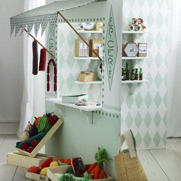 une petite épicerie comme un théâtre en bois pour enfant, pour jouer à la marchande avec des fruits et légumes en tissus des boîtes de pâtes, de fromages, de thé et café, de bonbons en trompe l'œil.