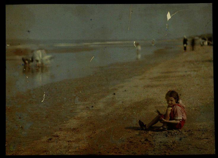 Meisje (gekleed in het rood, zittend) spelend aan het Noordzeestrand, met allerlei figuren op de achtergrond, anoniem, 1907 - 1930