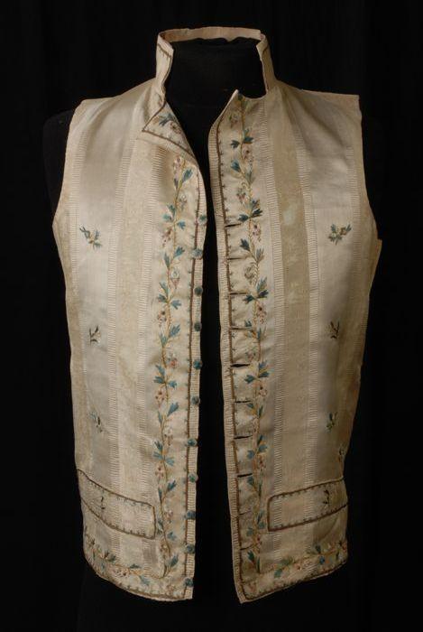 1794 HEREN-TROUWVEST, WIT ZIJDE GEBORDUURD MET BLOEMMOTIEFJE, ELF GEBORDUURDE KNOOPJES, WIT LINNEN ACHTERPAND, VOERING LICHTPAARS