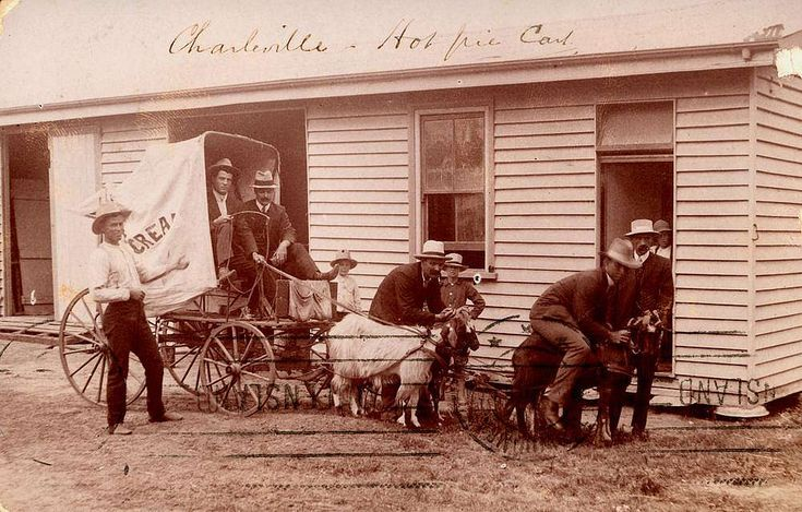 Group of 'big kids' playing on a Charleville pie cart drawn by goats, ca. 1909 - Group of men playing with the goat-team pulling a hot pie cart in Charleville, Queensland, around 1909. One of the men is pretending to ride one of the goats while younger boys look on. Copied from a postcard marked Charleville, 12 April 1910.