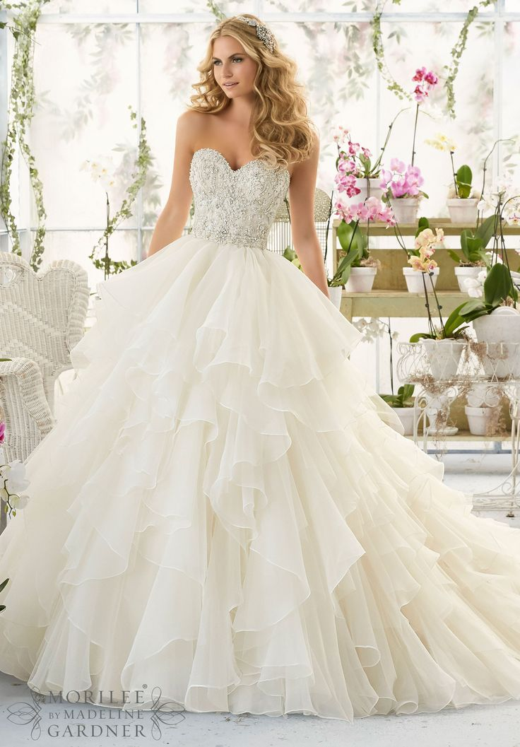 """Wedding Dresses and Wedding Gowns by Morilee featuring Intricate Crystal Beaded and Embroidered Bodice onto a Flounced Organza Skirt Removable Beaded Satin Belt. Available in Three Lengths: 55"""", 58"""", 61"""". Colors available:White/Silver, Ivory/Silver, Ivory/Light Gold/Silver, Ivory/Blush/Silver."""