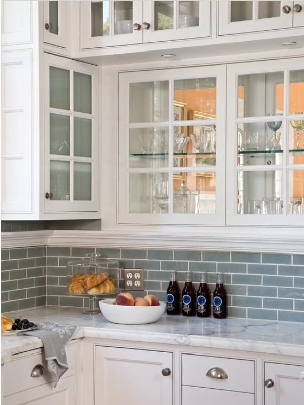 white cabinets with frosted glass, blue subway tile backsplash from