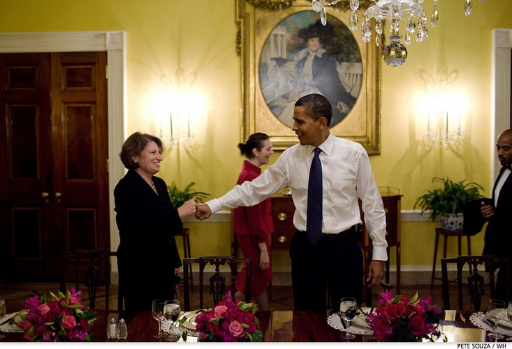 Obama fist-bumps with Susan Sher, Chief of Staff to the First Lady, while attending a women's dinner with staff in the Old Family Dining Room of the White House, Nov. 5, 2009.