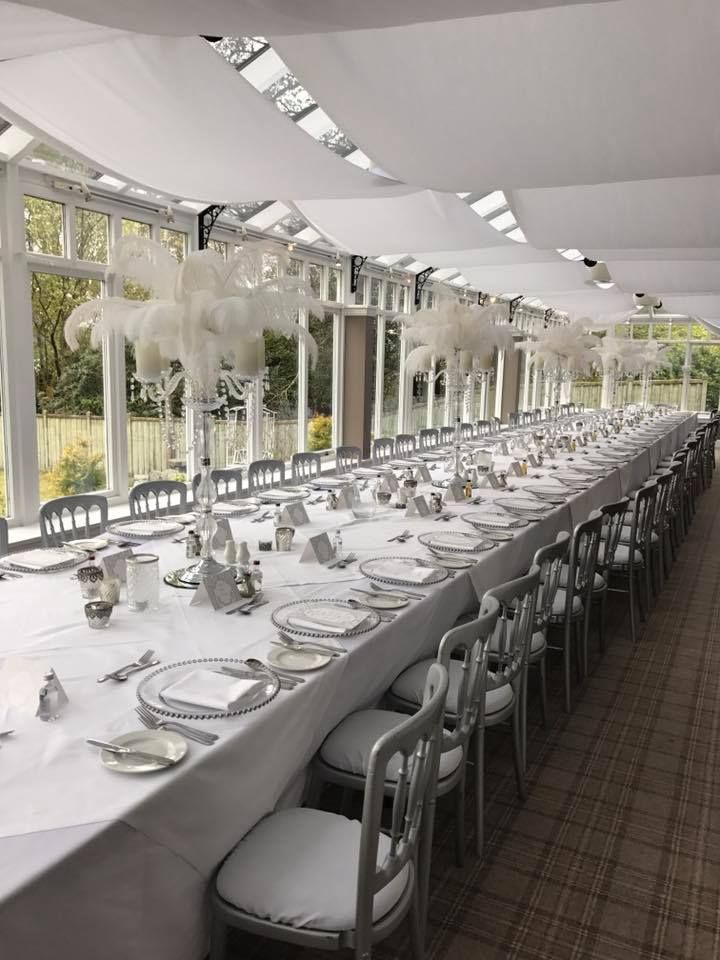 Great Gatsby Theme, Cheltenham Silver chairs white seat pads, Harrison Lane Crystal Candelabra topped with feathers and led candles, Glass silver beaded charger plates