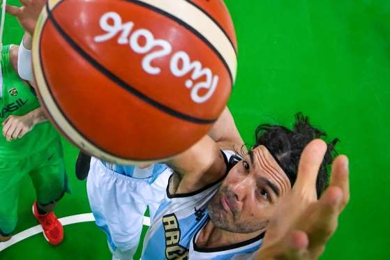 Argentina power forward Luis Scola (4) grabs a rebound over Brazil during the…