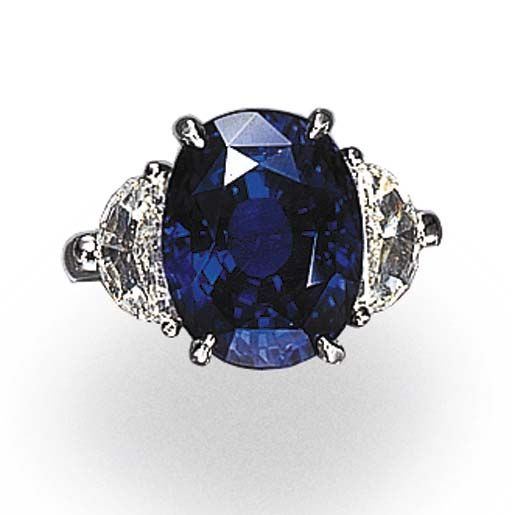 A SAPPHIRE AND DIAMOND RING   Set with an oval-cut sapphire weighing approximately 11.17 carats, flanked by half-moon-cut diamonds, mounted in platinum  [Nice stone!]