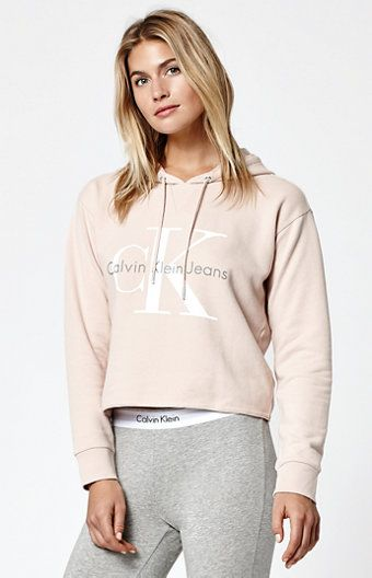 """Made from soft fleece, this Calvin Klein pullover hoodie has a modern, feminine fit. Washed in light pink, this pullover hoodie is complete with a drawcord hood, cozy long sleeves, ribbed cuffs, and a classic graphic on front.   Graphic on front Cropped cut Drawcord at the hood Model is wearing a small Model's measurements: Height: 5'10"""" Bust: 34"""" Waist: 24"""" Hips: 34"""" 60% cotton, 40% polyester Machine washable"""
