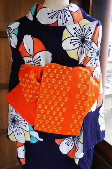 オレンジの地に、ブルーナの絵本のようなレトロポップキュートなお花模様が織り出された半幅帯です。