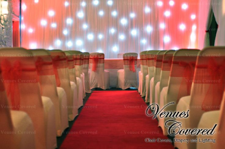 www.venuescovered.co.uk White chair covers with red organza sashes, white starlit backdrop and red uplighting