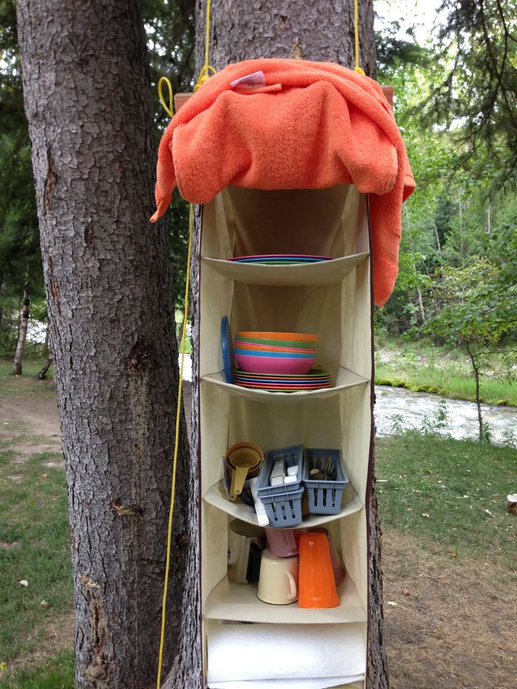 Hanging Organizer For Camping!  We bought ours at Army for $5. We just strung it up to a tree and filled it with all of our dishwear, cloths and cooking supplies (other than food obviously). When we are not at the campsite we just clothespin tea towels to the front like a door. It is so much easier than rummaging through a bin every meal! Genius idea mother, Genius!